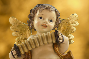 Angel with accordion on golden background