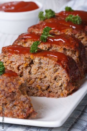 Poster sliced meat loaf with ketchup and parsley close-up