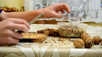 Teenager skilfully cracking walnuts with a knife