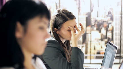 Woman in office feeling strong headache and tired