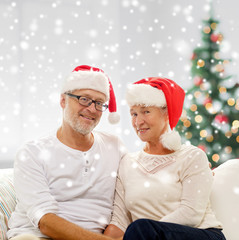happy senior couple in santa helper hats at home