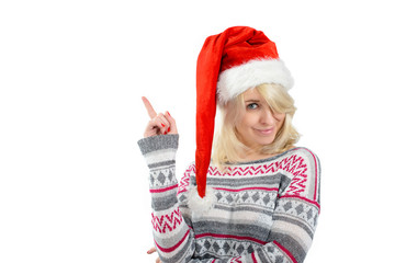 A cute woman in Santa's hat pointing up with finger