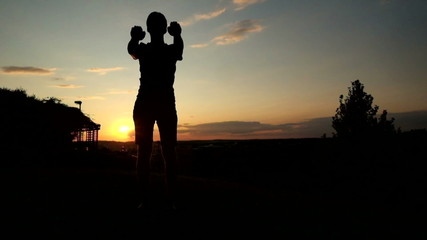 Silhouette of Young muscular man in tank top doing squats at