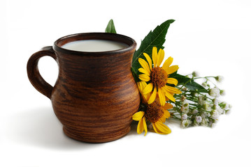 Milk in brown ceramic bowl and summer flowers