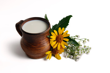Milk in brown ceramic bowl, summer flowers