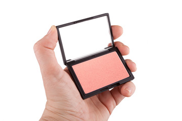 Female hand holding a peach and gold colored blush, isolated on