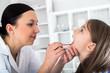 Doctor check throat of little girl