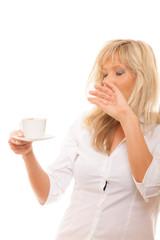 Sleepy tired woman yawning holds cup of coffee
