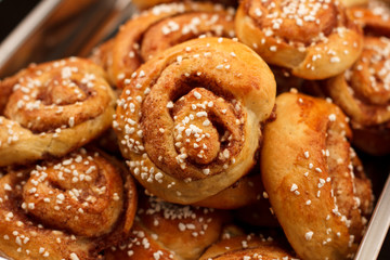 Cinnamon rolls in a metal container against a dark background