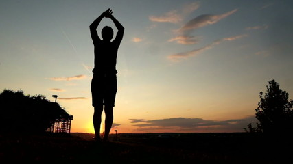 Young muscular man in doing jumpign jacks at park during sunset