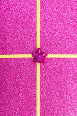 gold gift ribbon bow on purple shiny background