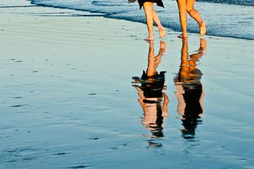 Side by Side - Two friends walking on the seashore