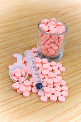 pink pills and syringe  on  table for health care concept