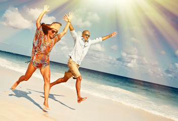 Happy couple running on the beach.