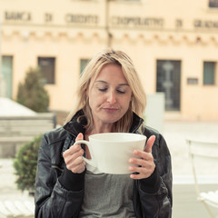 Sleepily girl drinking a large cup of coffee