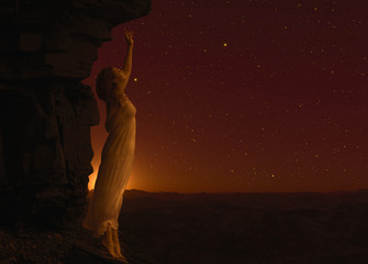 Woman standing on cliff's edge of another planet.