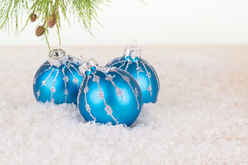 Blue Christmas baubles in snowflakes close-up