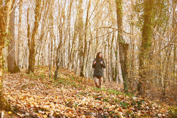 Hiker woman walking in autumn forest