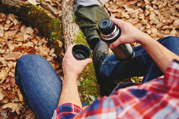 Hiker man holding thermos and cup of tea