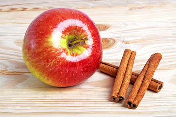 Red apple with cinnamon sticks on wooden background