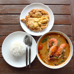 omelette,Tom Yam Kung,and steam rice on the wood table