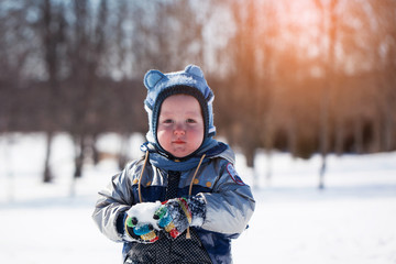 Adorable little boy at sunset on a beautiful winter day