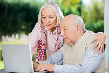 Serious Senior Man And Woman Using Laptop