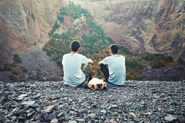Two young men sitting on rocky cliff