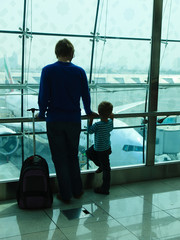 father and son looking at planes in the airport