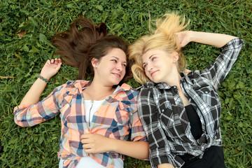 Blonde and brunette girl having rest on grass