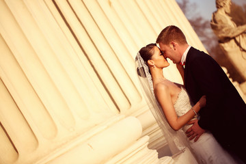 Bride and groom in a architectural place columns