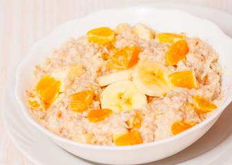 Bowl of oats porridge with banana and tangerine