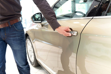 Mann öffnet einer Autotür im Autohaus