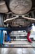 inside a garage - two mechanics working on a car, changing wheel