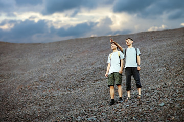Men standing on stones slope