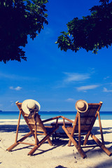 hats on chairs of tropical beach