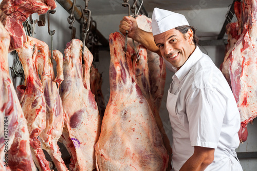 Butcher Standing By Meat Hanging In Slaughterhouse