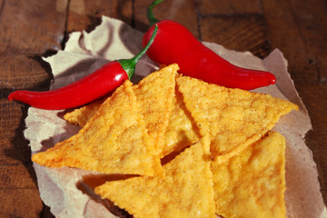Tasty nachos and chili pepper on paper, on wooden background
