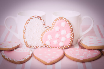 two cups and heart cookies on pink