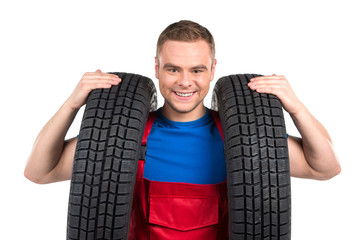 car mechanic carrying two tires on white background.