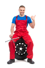 mechanic sitting on tire and showing thumb up.