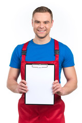 Young worker holding blank clipboard against white.