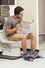 young relaxed man sitting on the toilet reading newspaper