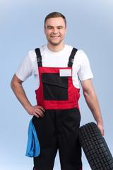 waist up portrait of mechanic holding spare tire.