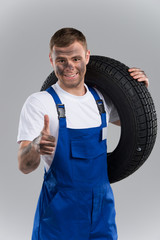 Mechanic holding vehicle tire on grey background.