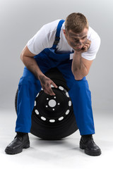man sitting on tire on grey background.