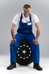 smiling man sitting on tire on grey background.