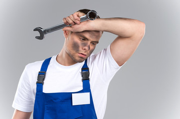 Tired young mechanic in blue overall on blue background.