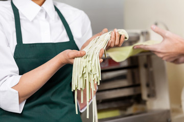 Female Chef Holding Spaghetti Pasta At Kitchen