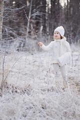 cute blonde child girl in white walking in snowy winter forest